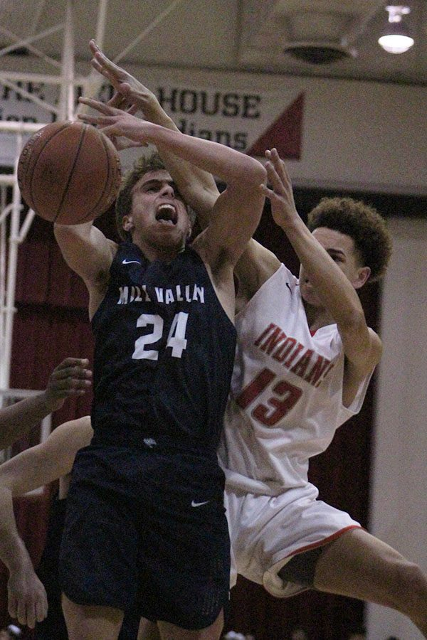 As junior Jack McGuire goes up for a layup, his opponent blocks him.