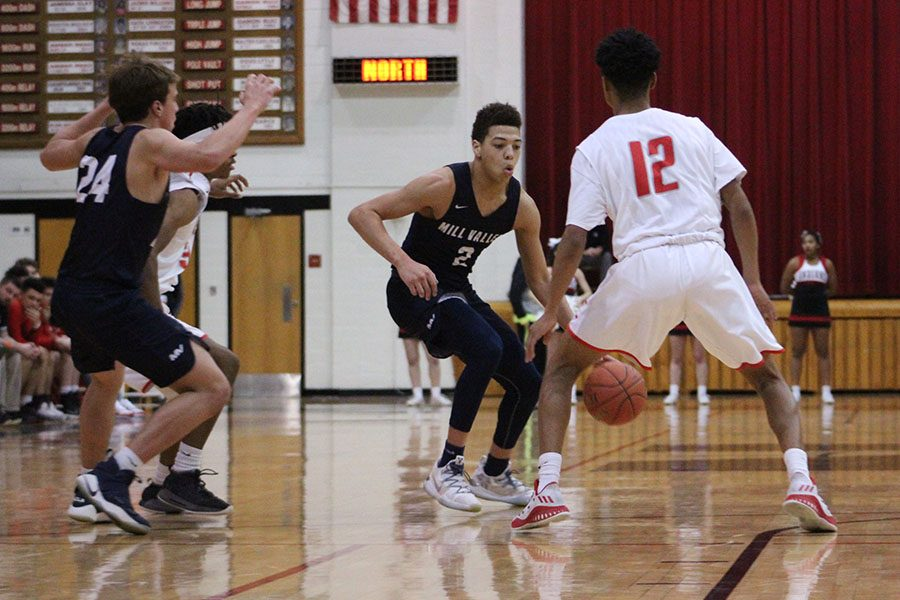 With two opponents trapping him, senior Matty Wittenauer dribbles past them.