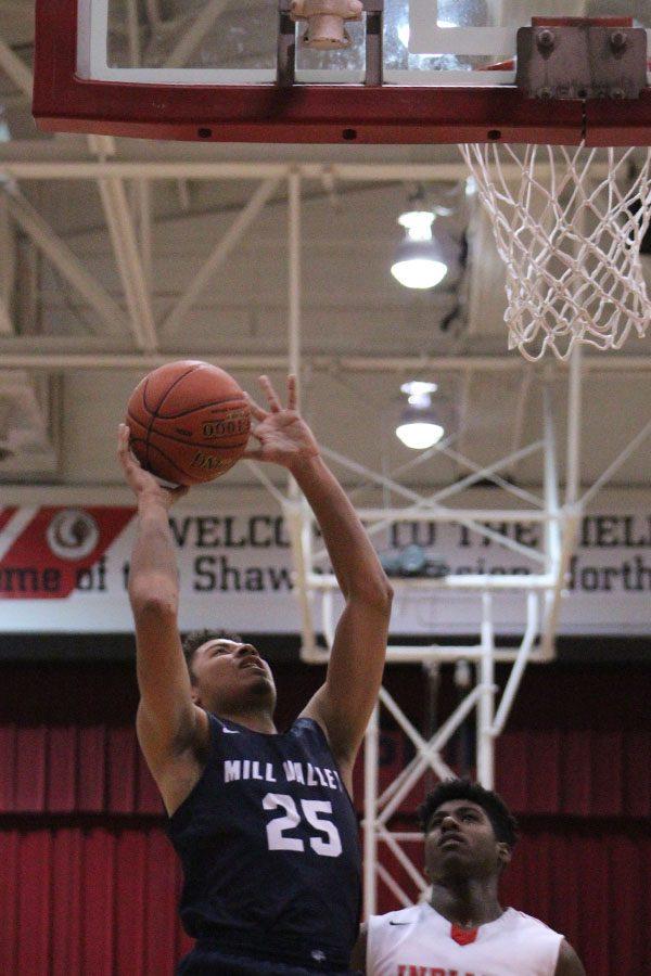 Looking towards the basket, senior Seth Hobson shoots the ball.