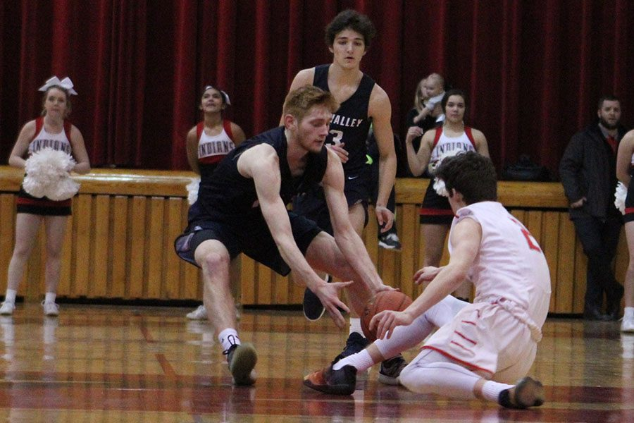 At half court, junior Braeden Wiltse tries to recover the ball from his opponent.
