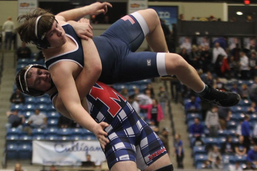 While in mid-air, sophomore Ethan Kremer's opponent takes him down.