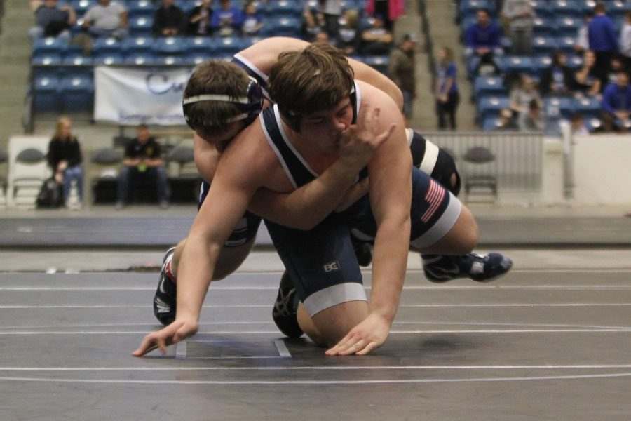 With his opponent on top of him, sophomore Ethan Kremer lifts up his back leg to break free.