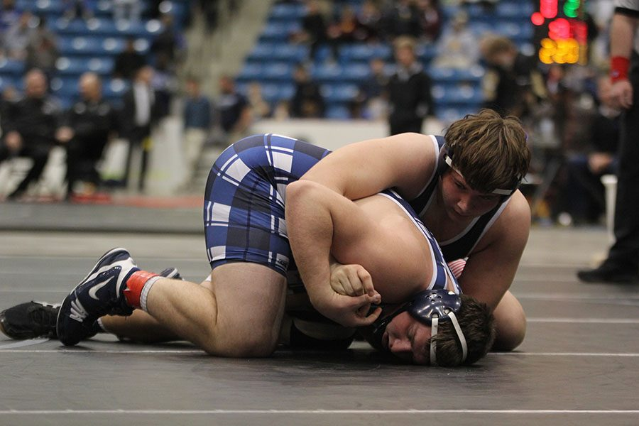 With his opponent under him, sophomore Ethan Kremer holds him in place.