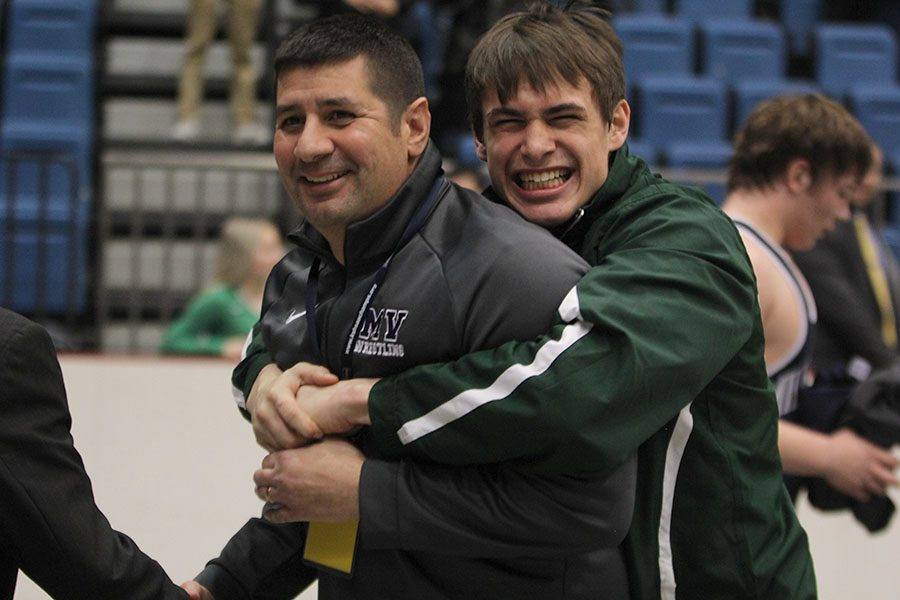After sophomore Ethan Kremer won a state title, a member of the Derby wrestling team congratulates head wrestling coach Travis Keal.