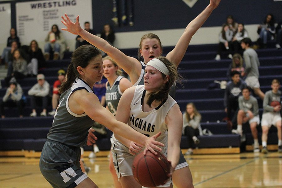 Trapped by defenders, senior Claire Kaifes attempts to hand the ball off.
