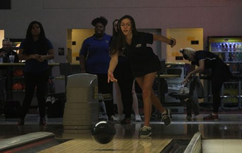 During warmups, sophomore Peyton Wagoner releases the bowling ball sending it town the pins.