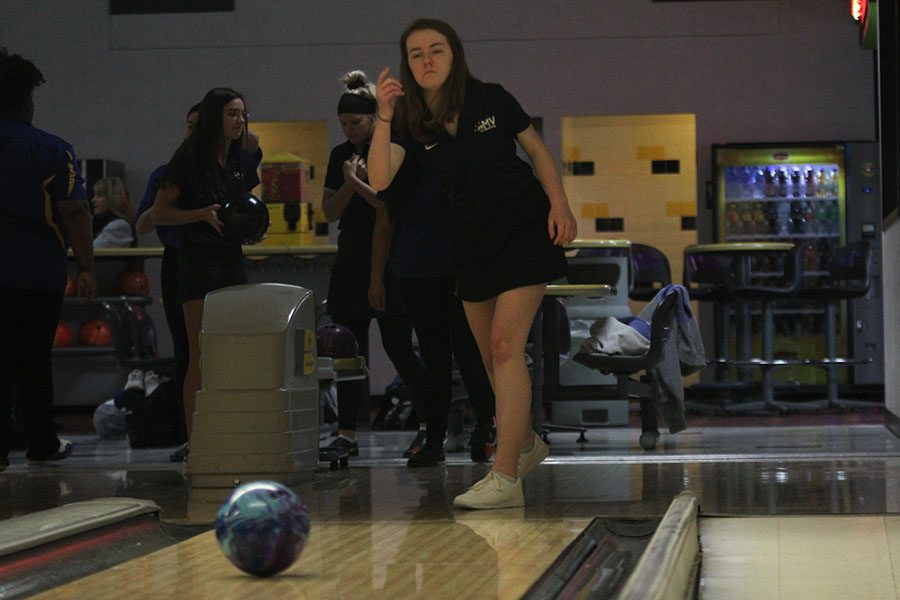 After letting go of her ball, junior Sydney Jackson watches her ball roll towards the pins.