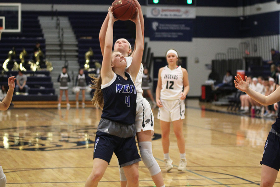 Reaching+to+strip+the+ball%2C+freshman+Emree+Zars+jumps+above+her+opponent.