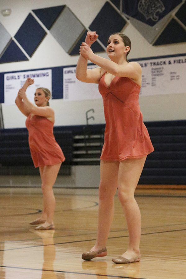 Performing in the sophomore ensemble, sophomore Kenzie Harris grabs her wrist.