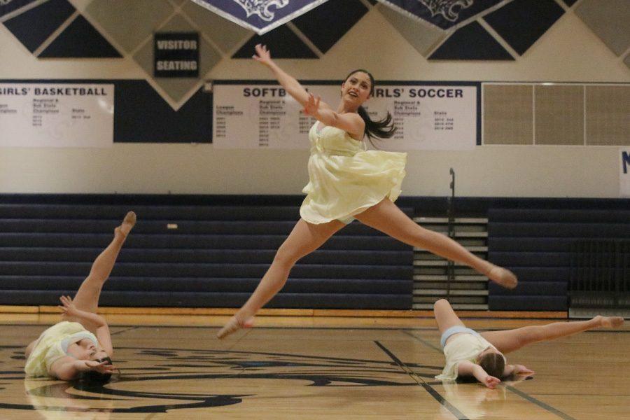 During the junior ensemble, junior Ali Greenhalgh leaps above juniors Sammie Pennington and Sydney Ebner.