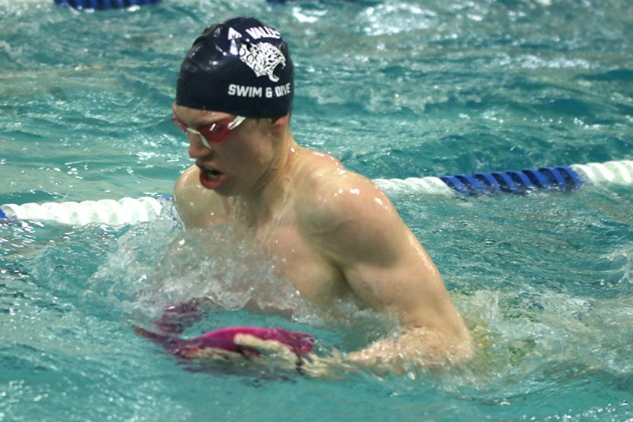 Swimming with paddles, senior Chris Sprenger practices his breast stroke form.