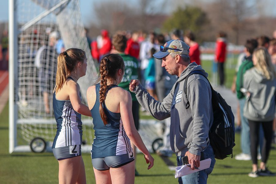 After finishing the 800-meter run, junior Molly Haymaker and senior Delaney Kemp give a fist bump to track head coach Chris McAfee.