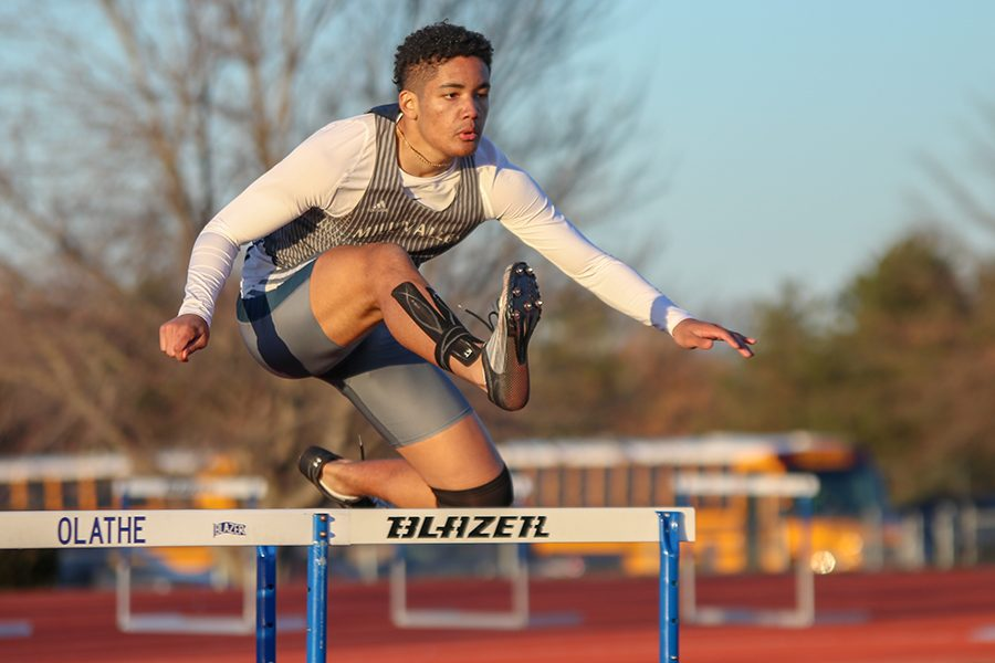 Competing in the 300-meter hurdles, junior Zach Mills continues sprinting down the track.