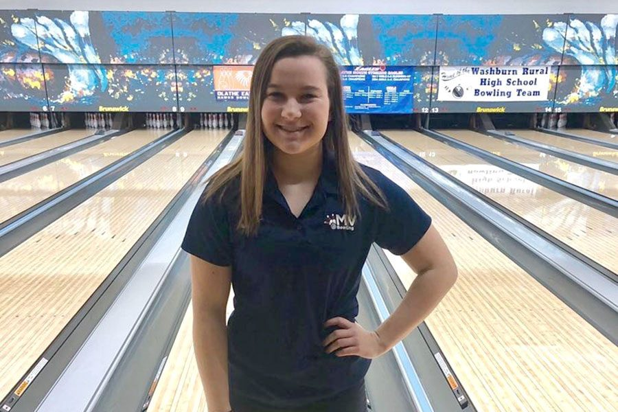 Before bowling at the state meet, junior Bri Laluk poses in front of the lanes.