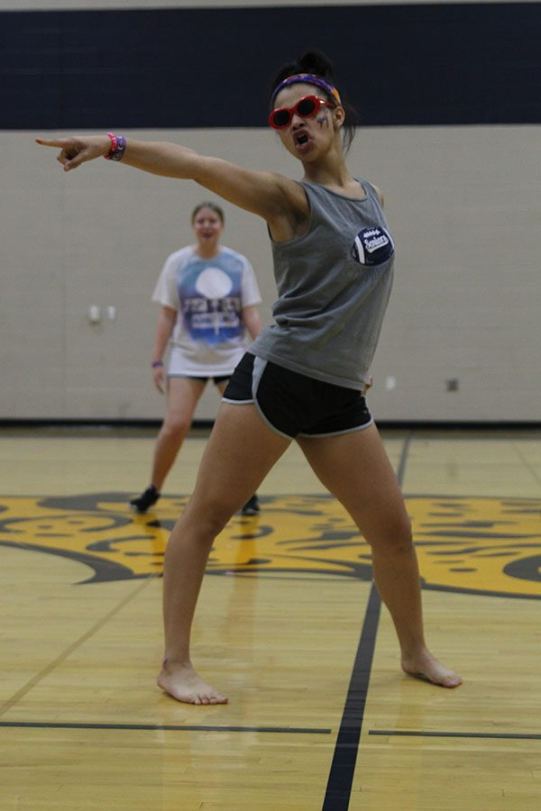 Pointing toward the audience, senior Lucy Graff competes in the lip sync battle.