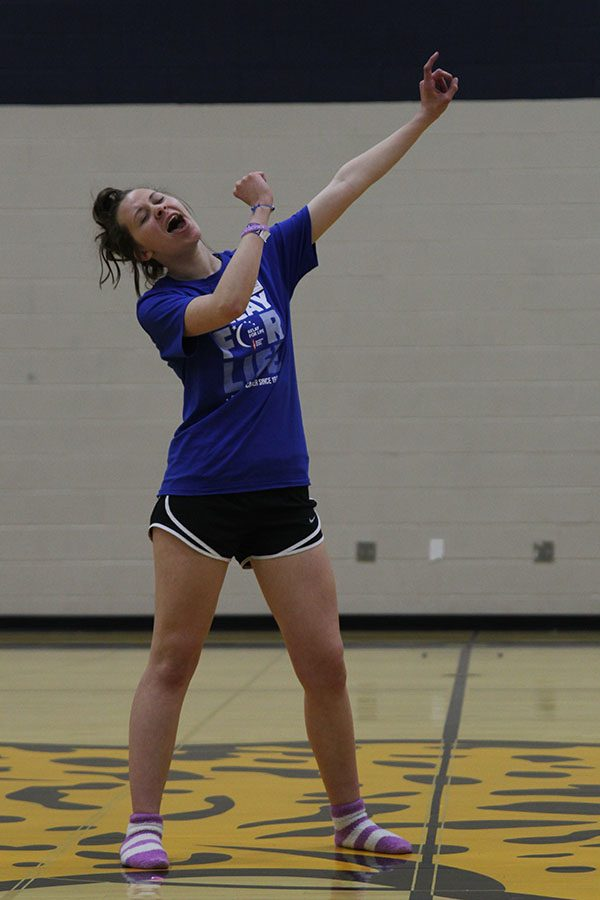 Holding up an imaginary microphone, freshman Alyssa Canning rocks out to