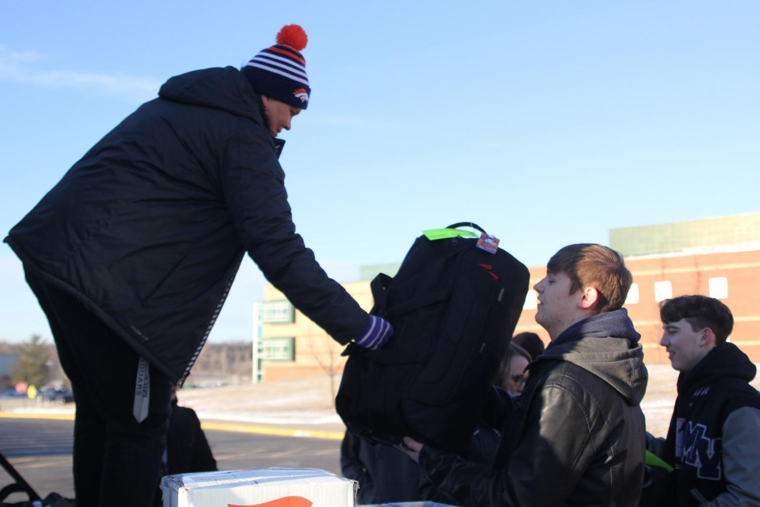"""Gathered around the back of a truck on Thursday, March 7, junior Jacob Howe help load instruments onto the truck for the """"You're Instrumental Workshop"""" at Disney World, so they can be transported with assistant band director Elca Wagner to Orlando, Florida."""