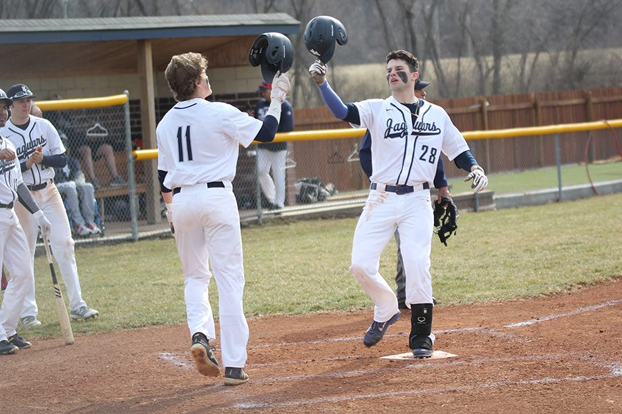 After his first home run, senior Quinton Hall is greeted at home plate by senior Cole Moore. The team defeated Veritas Christian 14-1 on Tuesday, Mar. 19.