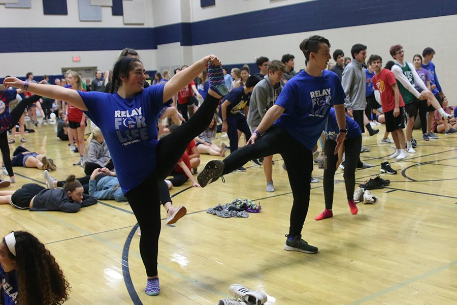 Trying to get into a yoga pose, sophomore Aaliyah Gonzalez and senior Johannes Seberger look to the instructor.
