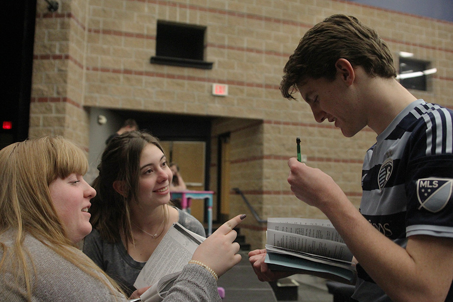 Looking over his script, sophomore Michael Brown receives notes from student directors sophomore Claire Burke and junior Chloe Griffin.