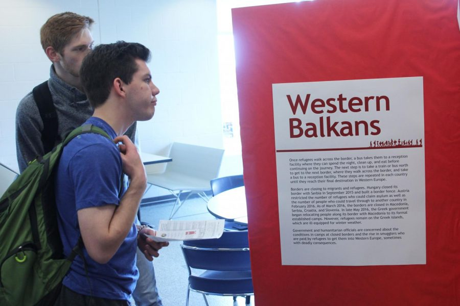 Hoping that the five items they chose at the beginning would help them survive, junior Braeden Wiltse and senior Tyler Jeanneret read information at the Western Balkans exhibit during the Youth for Refugees Simulation on Wednesday, March 27.