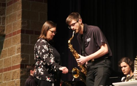 "During the song ""Hey Pachuco,"" junior Adam Tilden performs a tenor saxophone solo while band director Deb Steiner holds a microphone to amplify the sound at the jazz band concert on Monday, March 25."