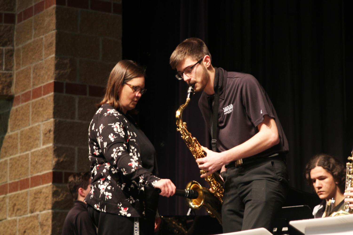 """During the song """"Hey Pachuco,"""" junior Adam Tilden performs a tenor saxophone solo while band director Deb Steiner holds a microphone to amplify the sound at the jazz band concert on Monday, March 25."""
