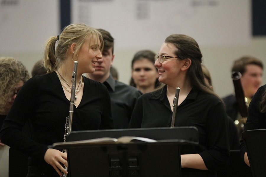 Talking after the concert, sophomore Meg Carey and junior Maddie Hodes set down their instruments.