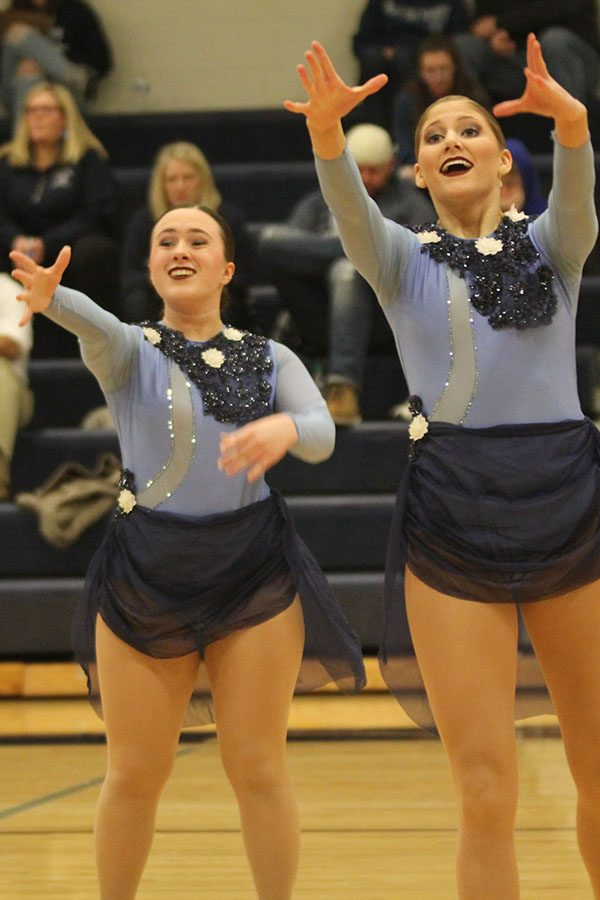 With arms reached out and expressive faces, seniors Eve Steinle and Addie Ward perform their routine at halftime of the girls basketball game on Thursday, Feb. 28.