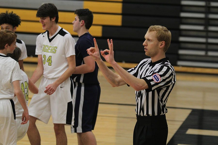 KSHSAA basketball referee Andrew Kremer signals a foul to the scorer's table during a freshman team boys basketball game against Blue Valley on Thursday, Feb. 21.  The Jaguars lost 49-48.