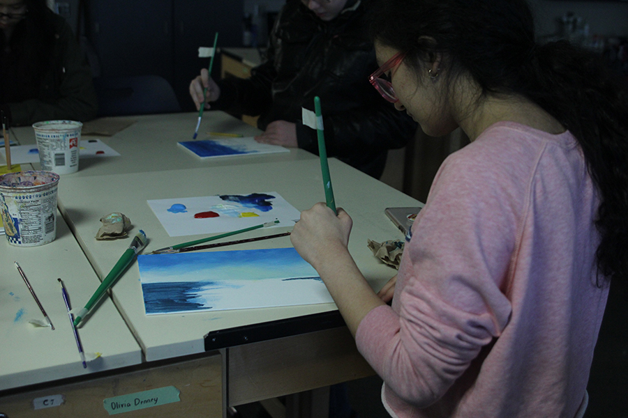 Holding her brush, freshman Natalia Hernandez paints along with Bob Ross.
