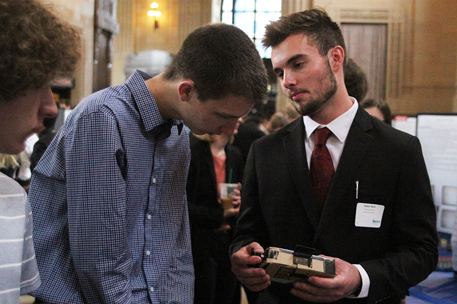 Demonstrating his project to an onlooker, senior Kaden Beck turns the knob on the side of his senior project, Cool Aide. The project seeks to keep refrigerated medications cold, which would be especially useful in areas seeking aid relief.
