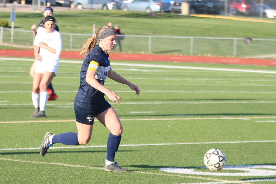 Making her way towards the ball, junior Emerson Kaiser turns back upfield.