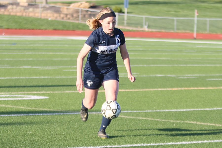 Dribbling her way towards the goal, junior Anna Ricker looks to extend the team's lead.