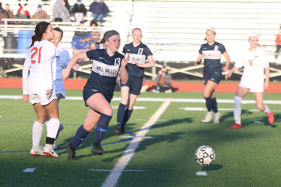 Making her way past two Shawnee Mission Northwest players, sophomore Paige Goetsch races towards the ball.