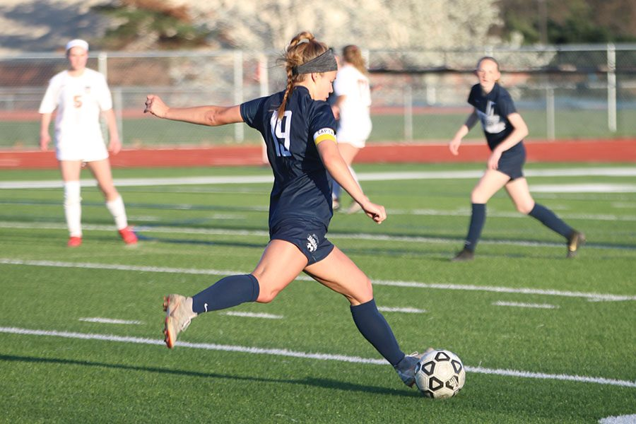 After getting the ball away from a Shawnee Mission Northwest player, junior Shyanne Best kicks the ball down the field.