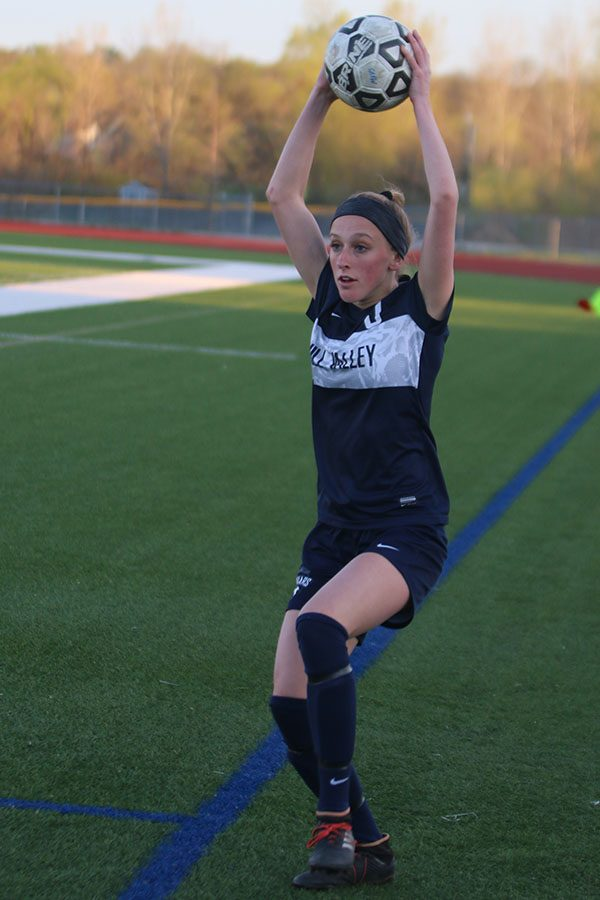 With the ball over her head, junior Annie Hoog throws the ball back in to her teammates.