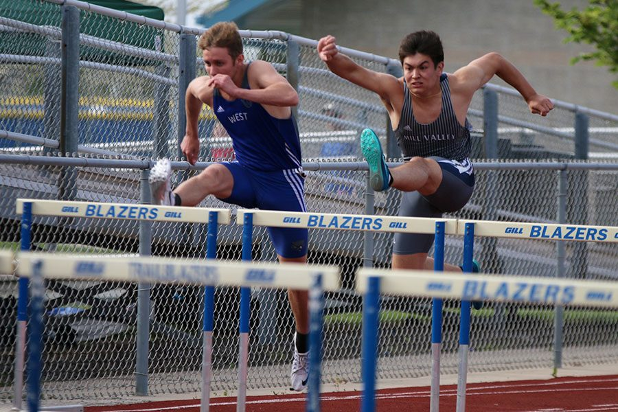 With his arms in the air, senior Eli Midyett jumps over a hurdle during the 110 meter hurdles race. Midyett finished fourth in the event.