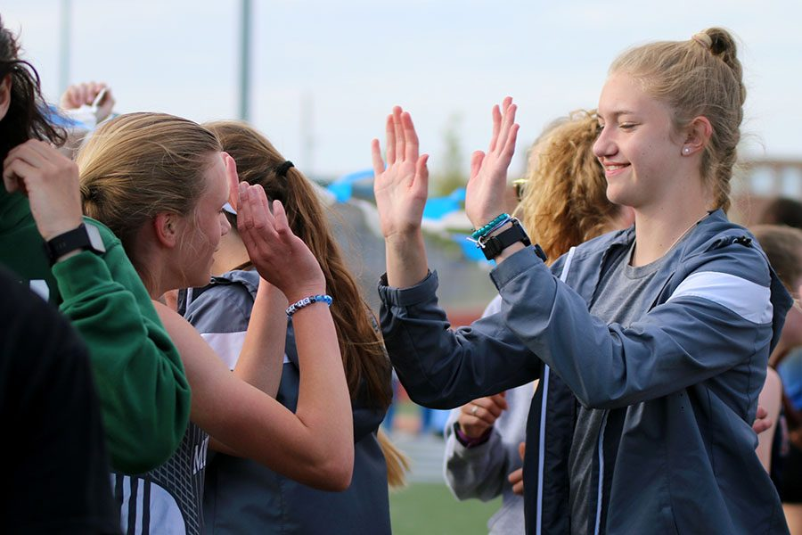 Holding her hands up for a high five on Friday, April 26, sophomore Josie Taylor congratulates freshman Katie Schwartzkopf on her run during the Trailblazer Invite.