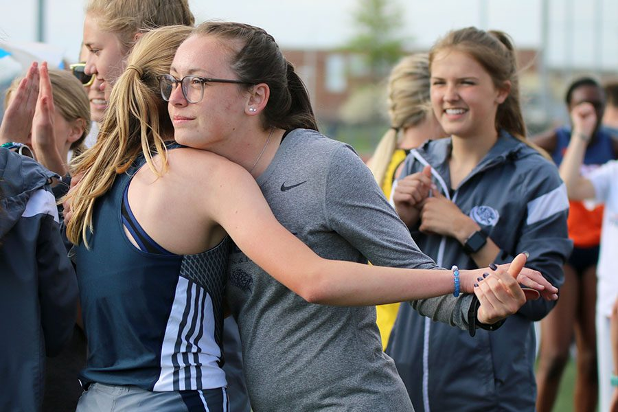 After the 1600 meter run, senior Delaney Kemp hugs freshman Katie Schwartzkopf as she comes off the field.