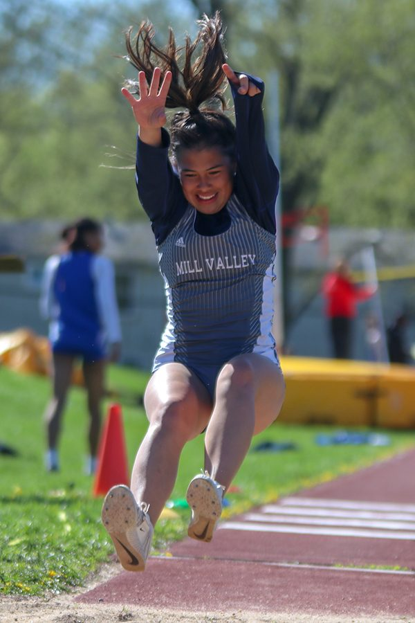 After running down the runway, senior Mya Johnston throws her arms and legs in the air to gain more distance in the triple jump.