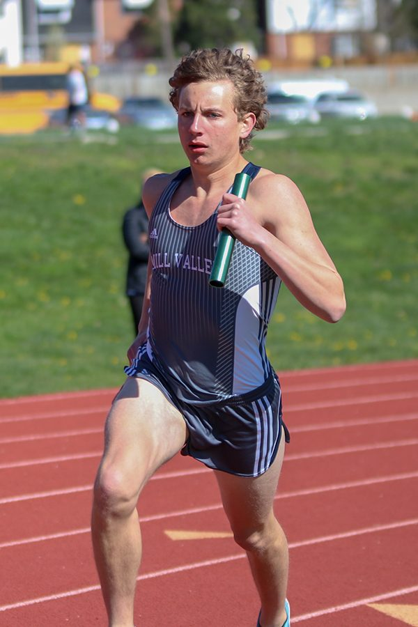 Carrying the baton in one hand, senior Jakob Twigg starts running his leg of the 4-by-800-meter relay.