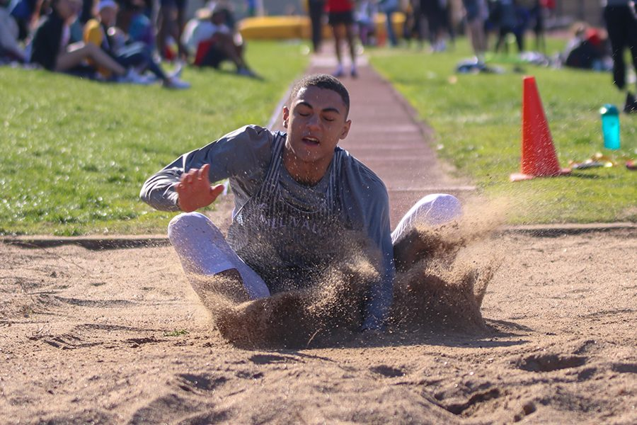 With his eyes closed, freshman Adrian Dimond competes in the long jump.