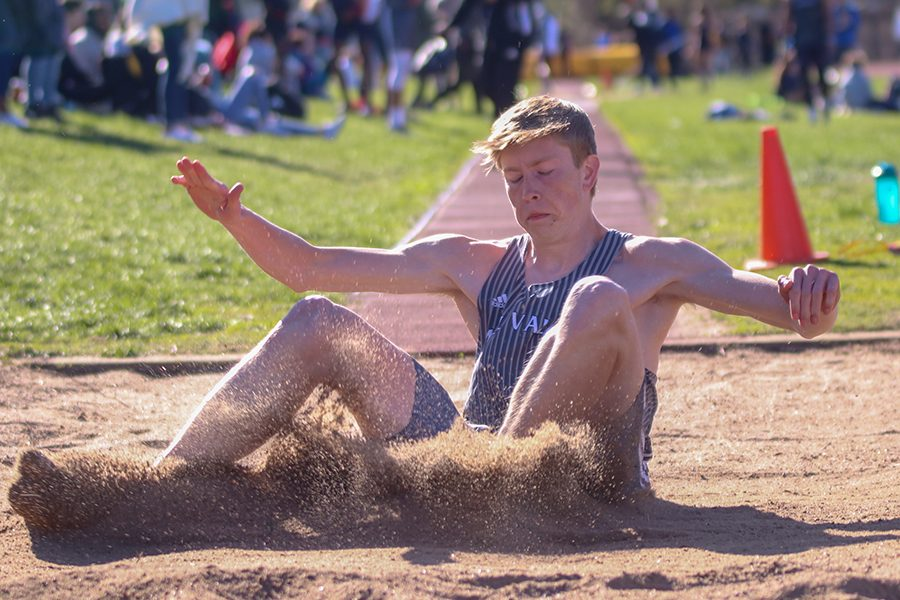 After running down the runway in the long jump, senior Harry Ahrenholtz lands in the sand pit.