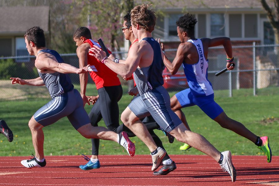 Completing the first leg of the 4-by-100-meter relay, senior Steven Colling hands the baton off to senior Henry Lopez.