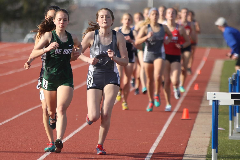 In+a+long+distance+event%2C+junior+Jenna+Walker+runs+head-to-head+alongside+her+competitors.