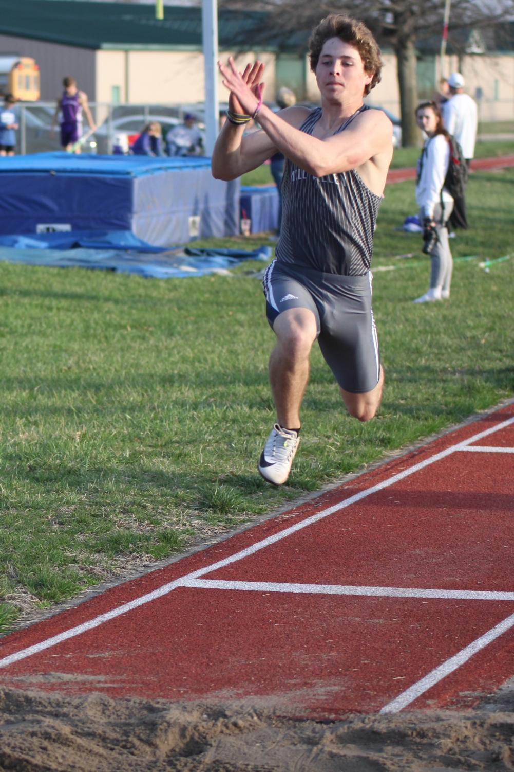 Jumping+forward%2C+senior+Steven+Colling+competes+in+the+long+jump+event.
