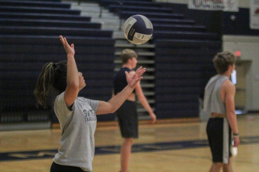 Preparing to serve, senior Mya Johnston tosses the ball into the air.