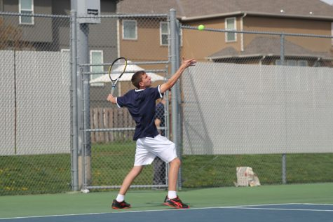 Throwing up the ball, sophomore John Scarpa serves the ball.