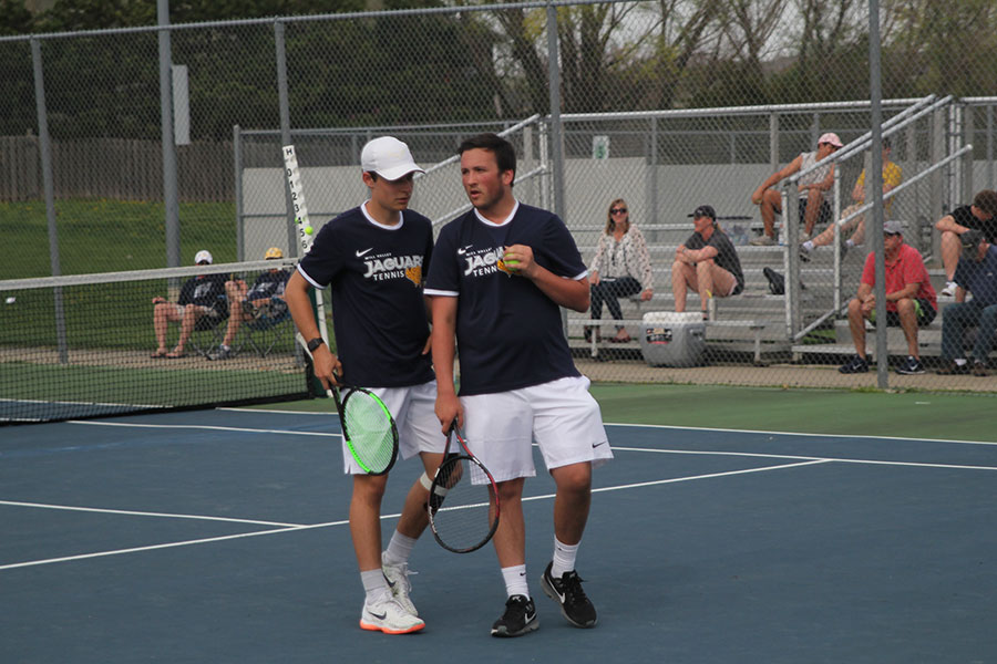 During+their+doubles+match%2C+freshman+Gage+Foltz+and+senior+Jacob+Hoffman+talk+in+between+points.+